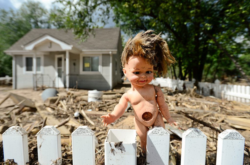 . A doll is seen stuck in a white-picket-fence near a home that is surrounded by mud and debris, Wednesday, Sept. 18, 2013, in Lyons.  (Matthew Jonas/Times-Call)