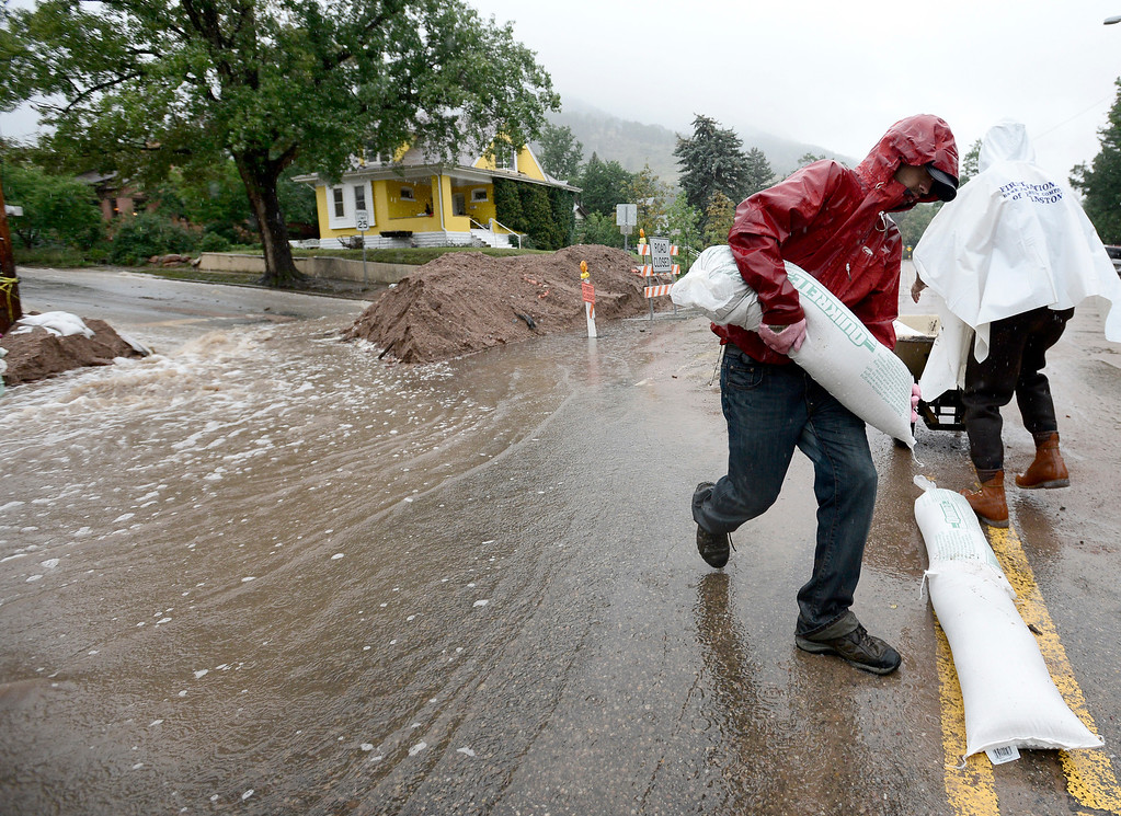 . Justin Hoffenberg adds sand bags to where rising water is beginning to run over 7th and University in Boulder, Colorado September 15, 2013.  REUTERS/Mark Leffingwell  (UNITED STATES)