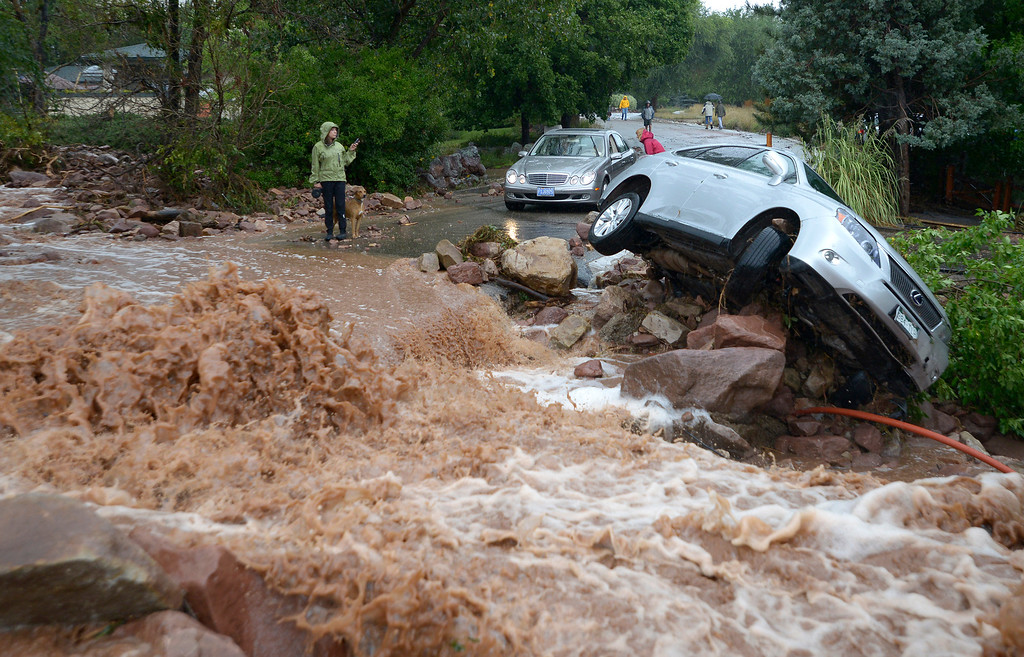 . People look at the overturned car near the fast moving water during the heavy flooding on Thursday in Boulder. For a video of the flooding go to www.dailycamera.com  Jeremy Papasso/ Camera