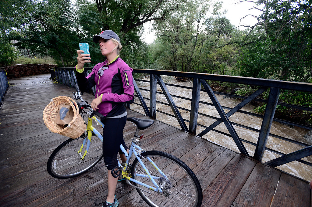 . Cassie King looks over Boulder Creek from a bridge in  Eben G. Fine Park in Boulder on Saturday.  Photo by Paul Aiken / The Daily Camera / Saturday September 14, 2013