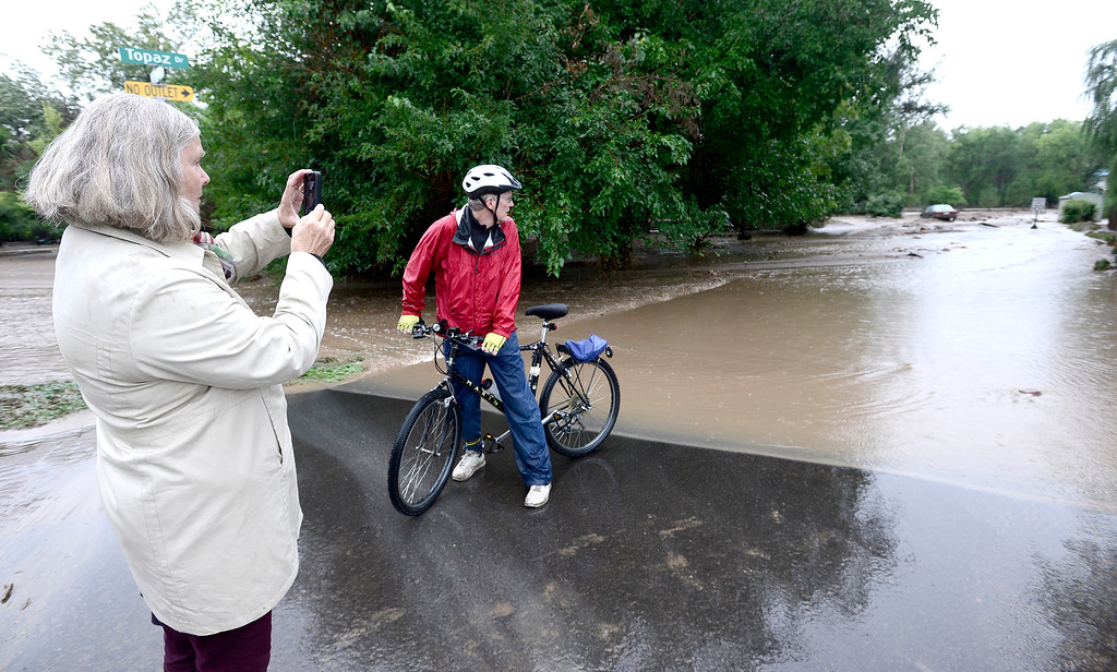 . Linda Jones takes photos with her phone while Tom Feiereisen (right) checks out the damage at 26th and Topaz Dr. after heavy rains caused serious flooding in Boulder, Colorado September 13, 2013. BOULDER DAILY CAMERA/ Mark Leffingwell