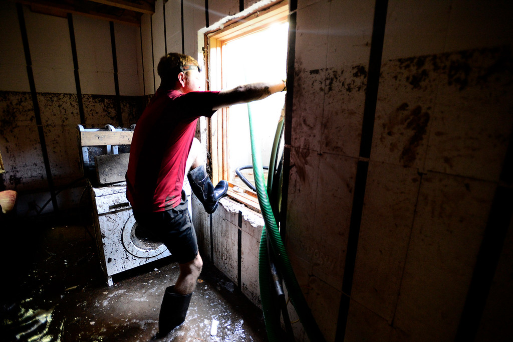 . Dean Beacom crawls in and out of his basement window as he tries to pump water out of his flooded Boulder, Colorado home.  Paul Aiken / The Daily Camera / Monday  September 16, 2013