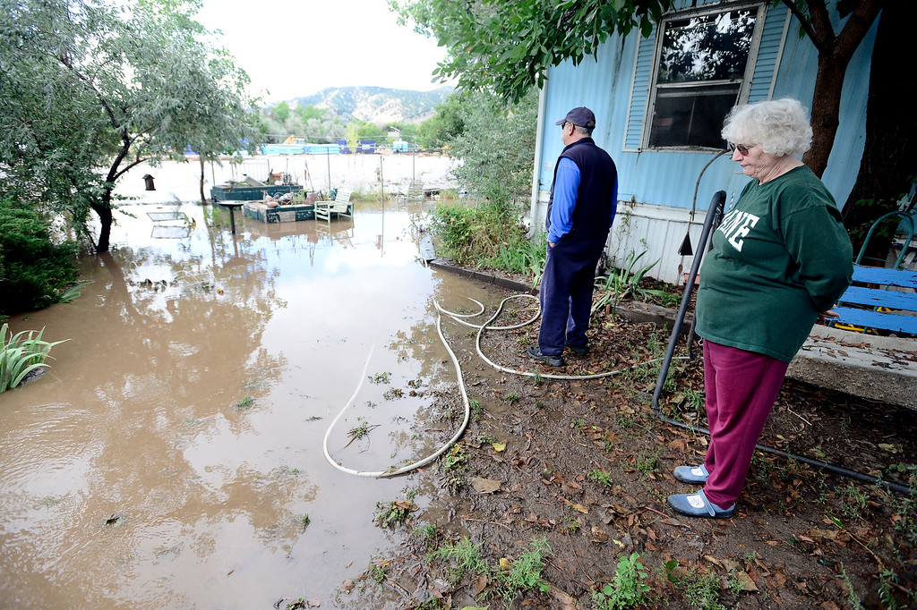 . Andy and Jo Ellen Terrell watch as the Fourmile Canyon Creek rises into their backyards. The creek was forced back into its back to stop it flowing into homes on its\' south bank but caused it to overflow the north bank.   Paul Aiken / The Daily Camera / Monday  September 16, 2013