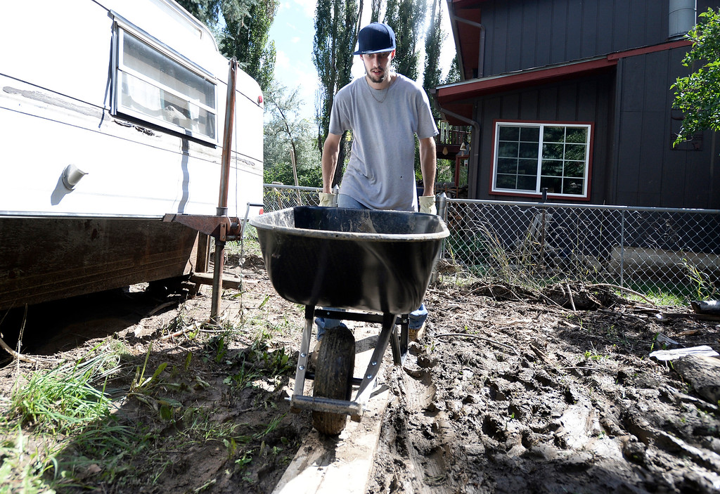 . Jestin Franklin pushes a wheelbarrow full of mud while helping his grandmother clean the flood damage on Tuesday, Sept. 17, in the Fourmile Canyon area of Boulder County. For more photos and video of the flood rescue go to www.dailycamera.com Jeremy Papasso/ Camera