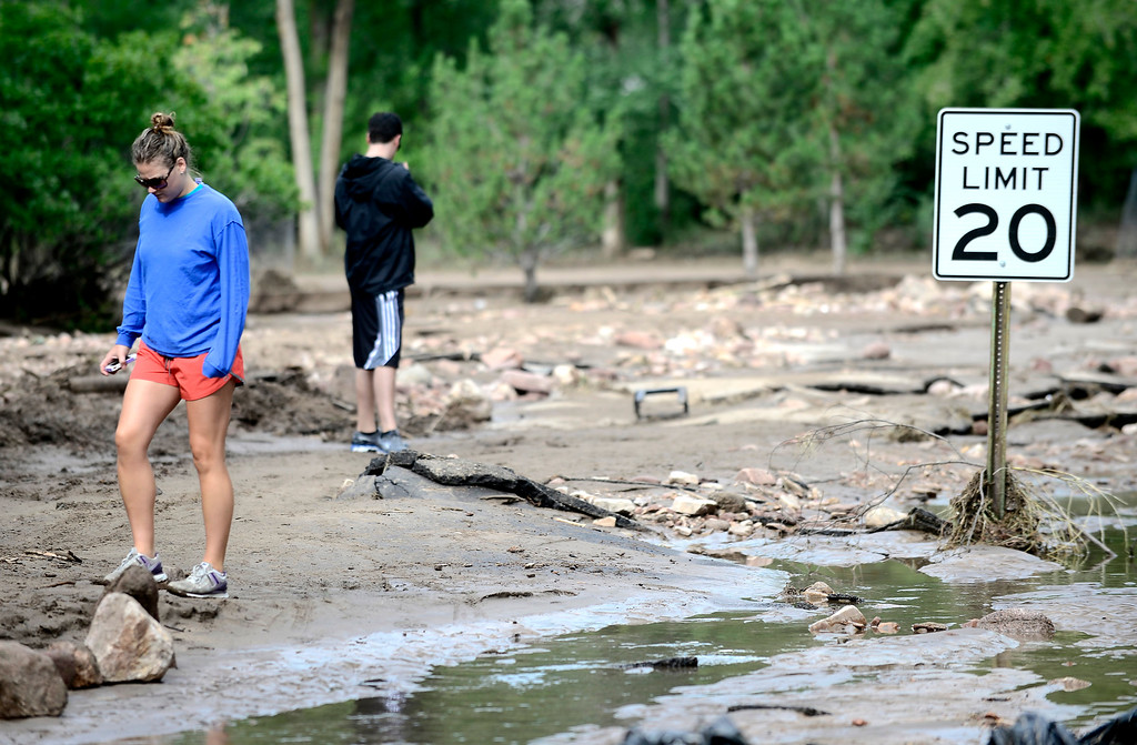 . Meg Faygen walks along a washed out Topaz Drive in Boulder on Saturday.  Photo by Paul Aiken / The Daily Camera / Saturday September 14, 2013