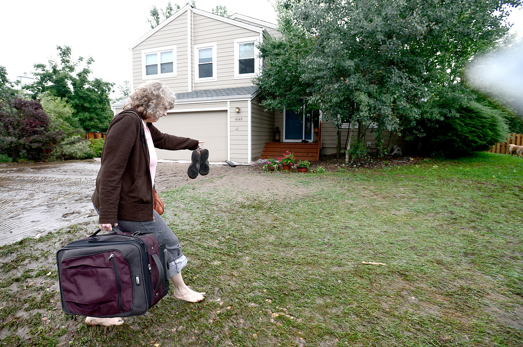 . Evelyn Moritz carries luggage back to her home after spending the night at friends after heavy rains caused severe flooding in Boulder, Colorado September 13, 2013. Moritz\'s home had mud up to the front door. BOULDER DAILY CAMERA/ Mark Leffingwell