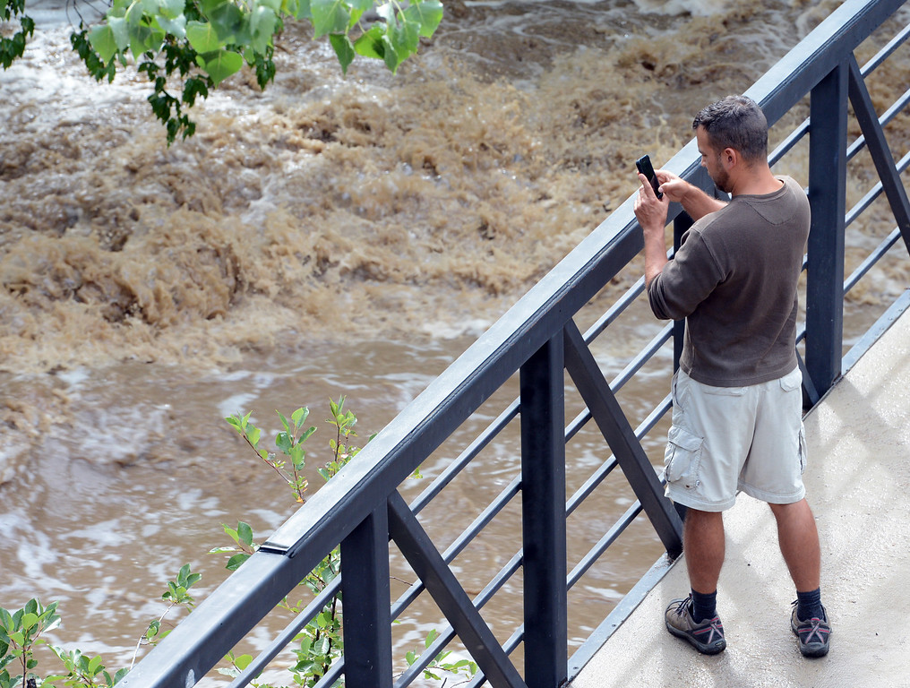 . A man takes a video of the raging Boulder Creek near Eben Fine Park on Friday.  For more flooding videos and photos, www.dailycamera.com. Cliff Grassmick  / September 13, 2013