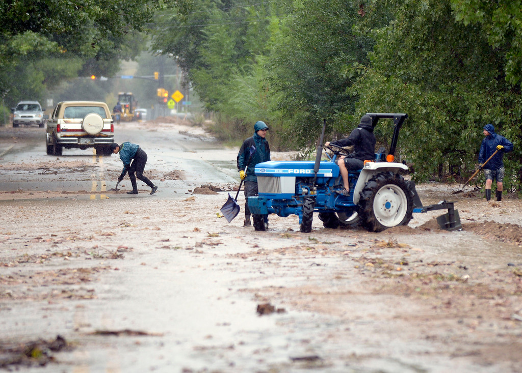 . Residents work together to clear debri and dig trenches to save a home from a flash flood on Sunday, Sept. 15, on Iris Avenue in Boulder. For more photos and video of the flood rescue go to www.dailycamera.com Jeremy Papasso/ Camera