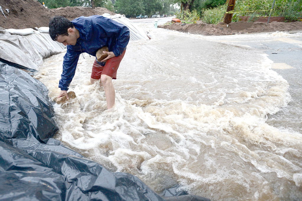 . Erez Shani adds rocks to hold plastic sheeting protecting a berm that is redirecting water as heavy rains cause flooding to rise in Boulder, Colorado September 15, 2013. BOULDER DAILY CAMERA/ Mark Leffingwell