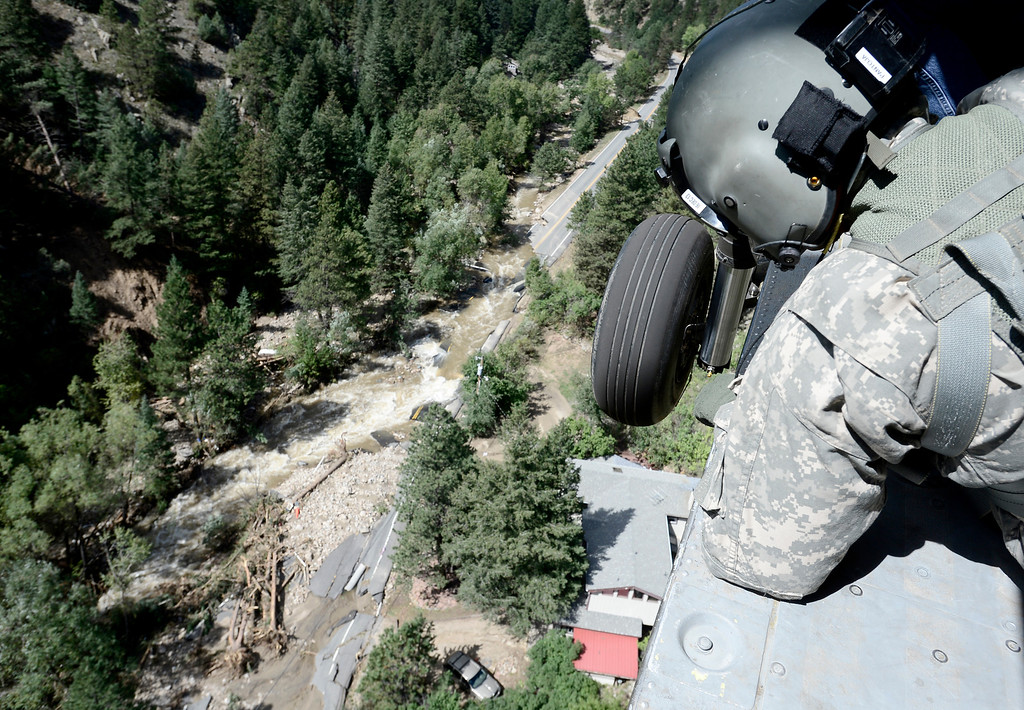 . Staff Sergeant Jose Pantoja, with the 2-4 GSAB 4th Infantry Division based in Ft. Carson, looks from the open door of a Blackhawk helicopter for people in need of help near Jamestown, Colorado September 17, 2013. BOULDER DAILY CAMERA/ Mark Leffingwell