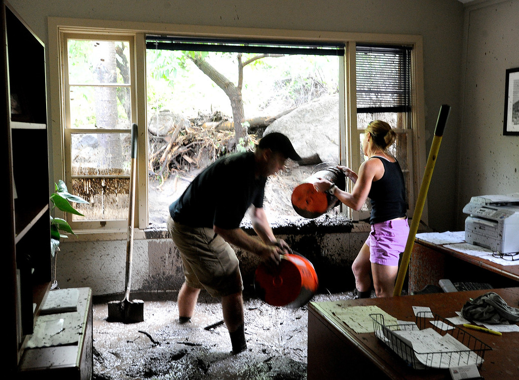 . Dave Naber, left, and Kelly Schultz, shovel out mud and water out of one of the Farmer\'s Insurance offices on west Arapahoe on Friday. For more flooding videos and photos, www.dailycamera.com. Cliff Grassmick  / September 13, 2013