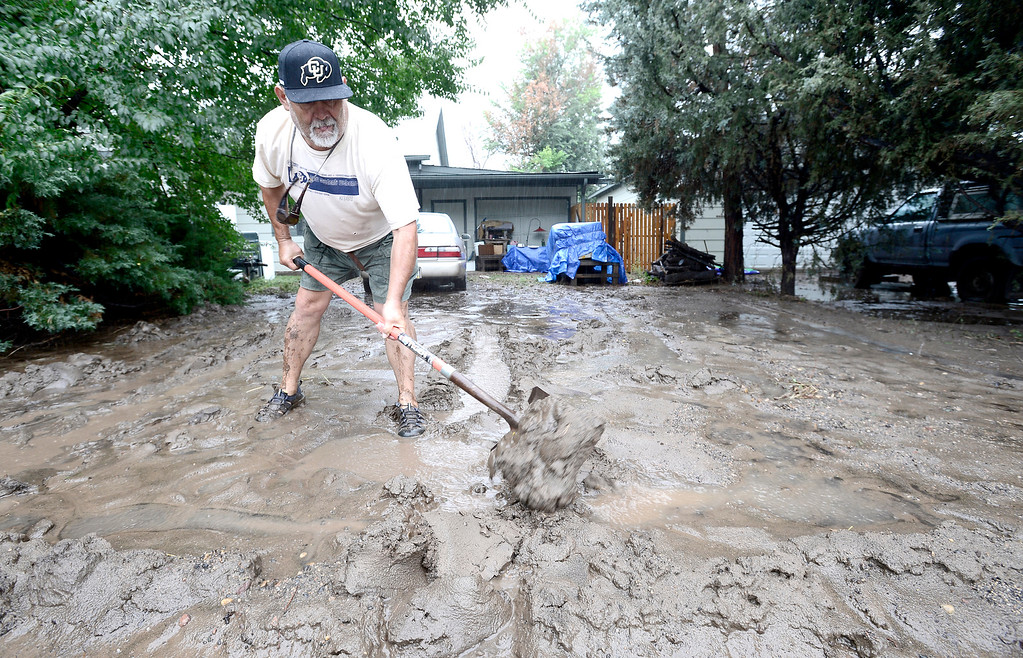 . Rich Luna tries to make a mud barrier in front of his house near 19th and Violet as heavy rains cause flooding in Boulder, Colorado September 12, 2013. BOULDER DAILY CAMERA/ Mark Leffingwell