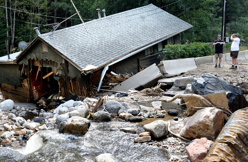 . People stand next to a destroyed home in Salina  on Tuesday, Sept. 17, on Fourmile Canyon Drive near Boulder Colorado. For more photos and video of the flood rescue go to www.dailycamera.com Jeremy Papasso/ Camera