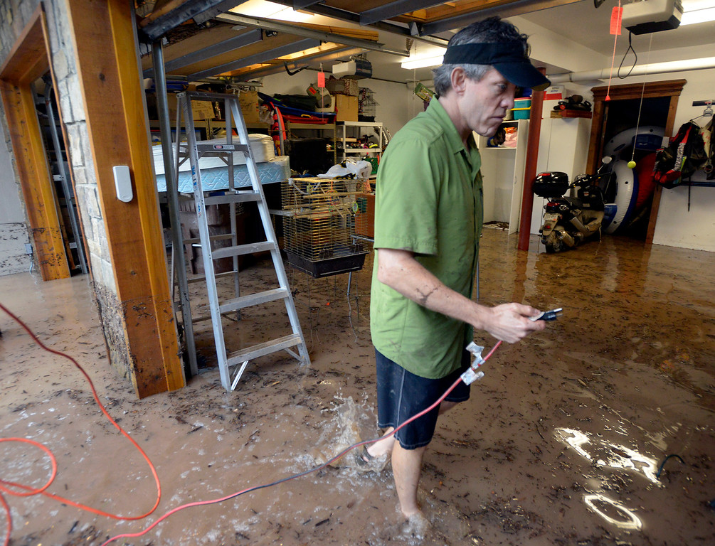 . Chris Drummond looks for a working electrical outlet while trying to set up water pumps to pump out his basement during the heavy flooding on Thursday in Boulder. For a video of the flooding go to www.dailycamera.com  Jeremy Papasso/ Camera