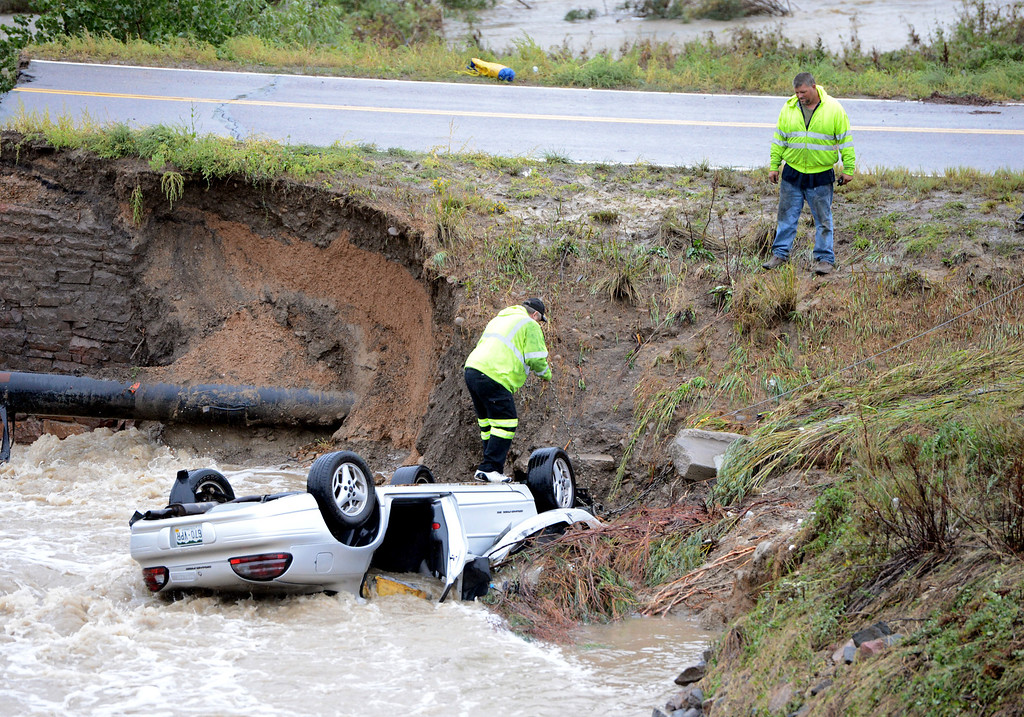 . Tow truck staff attach a cable to one of the cars. A bridge collapse on a business access road at Highway 287 and Dillon Road in Lafayette causes 3 cars to fall in the creek. Cliff Grassmick / September 12, 2013