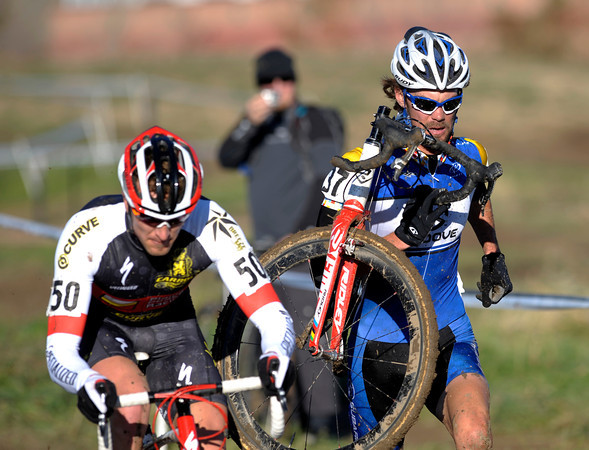 """1030CUP5.jpg William Iaia (right) passes Scott Tietzel (left) carrying his bike through the mud during the Men's Elite race of The Boulder Cup at the Valmont Bike Park in Boulder, Colorado October 30, 2011.  CAMERA/Mark Leffingwell<br /> <br /> Watch video from The Boulder Cup at  <a href=""""http://www.dailycamera.com"""">http://www.dailycamera.com</a>"""