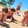 Left to Right, Adam Devon, Dominique Bustamante and Nyomi Davis play in the sand as Lisa Bustamante looks on at Boulder Reservoir Tuesday.