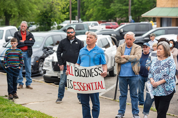 """Glen Thurman, owner of Rose Hill Apartments in Mineola holds a sign reading """"All business is essential"""" during a rally of people who want to see business restrictions loosened in sight of coronavirus restrictions and their effect on the local economy at the Wood County Courthouse in Quitman, Texas on Friday, April 17, 2020. About 40 people attended the event."""