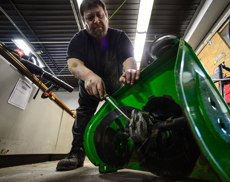 KRISTOPHER RADDER — BRATTLEBORO REFORMER<br /> David Judd, owner of Judd's Power Equipment, in Westminster, adjusts the blades on a snowblower.