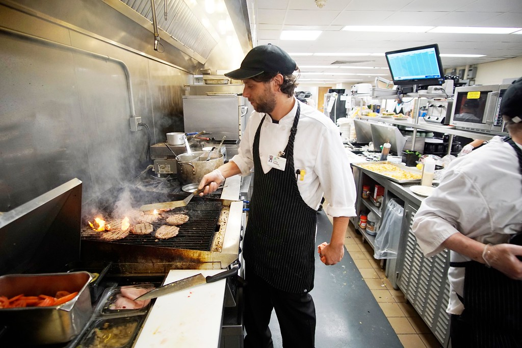 ". BMC cook Corey Plankey makes burgers at the hospital kitchen, Thursday, August 4, 2016. ""It is hard to keep up with me, I do five things at once.\""  Ben Garver � The Berkshire Eagle 
