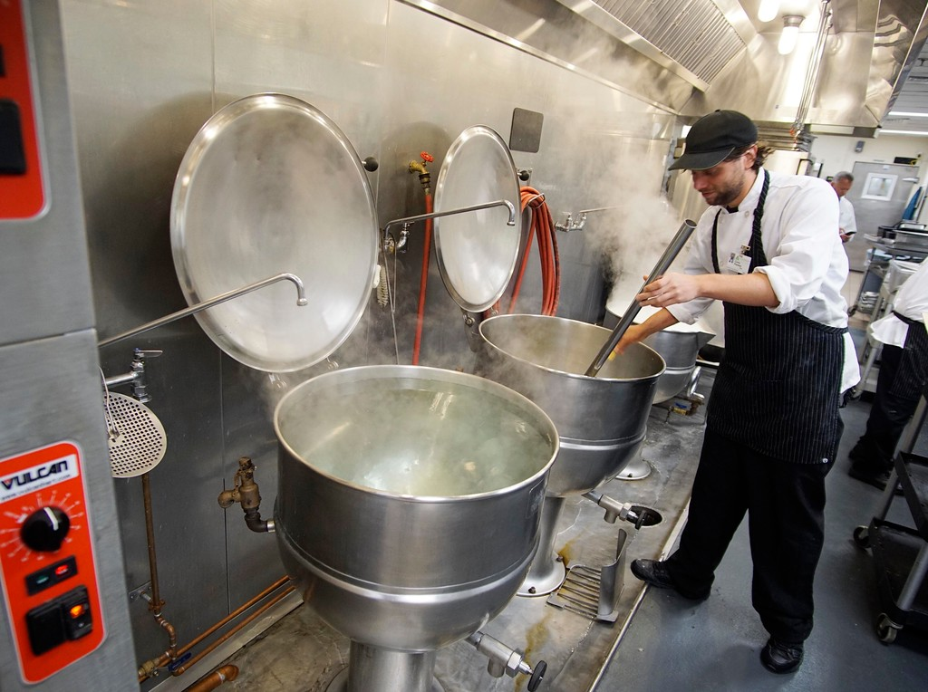 ". BMC cook Corey Plankey checks broth at the hospital kitchen, Thursady, August 4, 2016. ""It is hard to keep up with me, I do five things at once.\""  Ben Garver � The Berkshire Eagle 