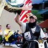 "Kevin ""The Liberal"", last name not given, gets a high-five from Captain Obvious while riding his Big Wheel on Saturday, July 9, during the Big Wheel Rally in Boulder. For more photos and video go to  <a href=""http://www.dailycamera.com"">http://www.dailycamera.com</a><br /> Jeremy Papasso/ Camera"