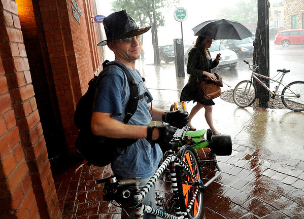 "Scott Gilleon, of Boulder, ducks out of the rain while towing his Big Wheel behind his bicycle on Saturday, July 9, during the Big Wheel Rally in Boulder. For more photos and video go to  <a href=""http://www.dailycamera.com"">http://www.dailycamera.com</a><br /> Jeremy Papasso/ Camera"