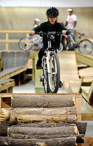 Zackary Schindler, 8, heads down the log obstacle during the mountain bike clinic at Boulder Indoor Cycling in Boulder, Colorado December 15, 2009.  CAMERA/Mark Leffingwell
