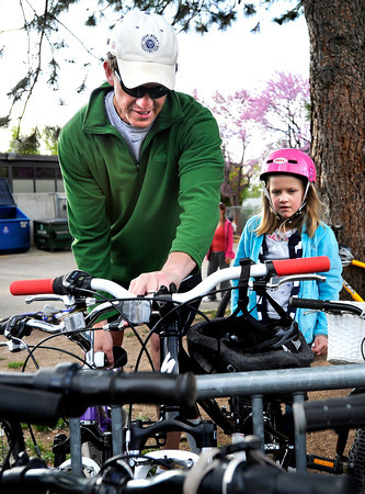 """Doug Rutherford helps his daughter Petra put her bicycle in the bike rack during bike-to-school day on Thursday, April 19, at Foothills Elementary School in Boulder.For more photos and video of bike-to-school day go to  <a href=""""http://www.dailycamera.com"""">http://www.dailycamera.com</a><br /> Jeremy Papasso/ Camera"""