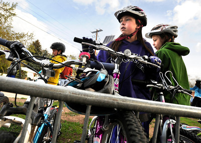 Third-graders Abbie Gillach, center, and Olivia Dawson, right, park their bicycles in the bike rack during bike-to-school day on Thursday, April 19, at Foothills Elementary School in Boulder. For more photos and video of bike-to-school day go to www.dailycamera.com Jeremy Papasso/ Camera