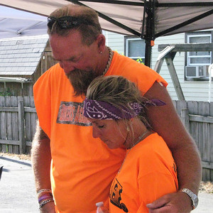 BOB SANDRICK / GAZETTE Scot and Patti Neufer, founders of Bikers Against Heroin, have a moment of silent prayer Saturday in Lodi after the motorcycle poker run.
