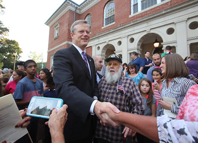 Gov. Charlie Baker signs a bill declaring that Billerica is Yankee Doodle Town, during a ceremony at the Billerica Public Library. Gov. Charlie Baker, next to Billerica Santa Claus Chuck Graham of Billerica, shakes hands after the ceremony. (SUN/Julia Malakie)