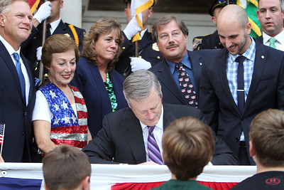 Gov. Charlie Baker signs a bill declaring that Billerica is Yankee Doodle Town, during a ceremony at the Billerica Public Library. Looking on are, from left, selectman John Piscatelli, Carol Rosa (mother of former selectman Michael Rosa), selectman Kim Conway, former selectman Michael Rosa, and State Rep. Marc Lombardo. (SUN/Julia Malakie)