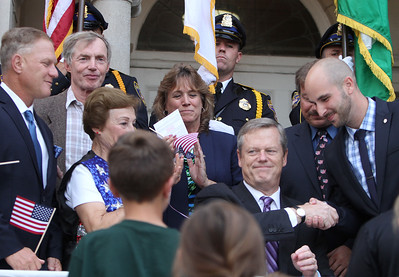 Gov. Charlie Baker signs a bill declaring that Billerica is Yankee Doodle Town, during a ceremony at the Billerica Public Library. Charlie Baker shakes hands with State Rep. Marc Lombardo after signing the bill. Looking on are Selectmen, from left, John Piscatelli, George Simolaris and Kim Conway, and Carol Rosa (mother of former selectman Michael Rosa) in stars and stripes vest. (SUN/Julia Malakie)