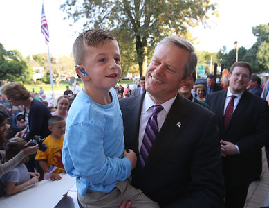 Gov. Charlie Baker signs a bill declaring that Billerica is Yankee Doodle Town, during a ceremony at the Billerica Public Library. Gov. Charlie Baker poses for a photo with James Swift, Jr., 7, of Billerica, a first grader at the Ditson School. (SUN/Julia Malakie)