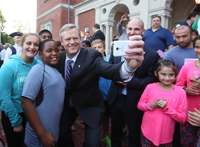 Gov. Charlie Baker shoots selfies with attendees after signing a bill declaring that Billerica is Yankee Doodle Town, during a ceremony at the Billerica Public Library.  (SUN/Julia Malakie)