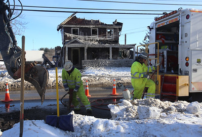 Scene of fire at 29 Andover Road, Billerica, home of Rome Capobianco, who died in the January 21 fire. National Grid workers dig in the street to disconnenct gas at the main. The service had been disconnected last night. (SUN/Julia Malakie)