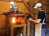 HOLLY PELCZYNSKI - BENNINGTON BANNER Fourth grade elementary school teacher Charlie Cummings stokes the fire and heats up coal to hand forge metal to make decorative  objects in his blacksmithing studio on Wednesday in Arlington.