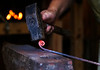 HOLLY PELCZYNSKI - BENNINGTON BANNER Wrought iron  is forged into a fiddlehead on Wednesday morning in the studio of Charlie Cummings, fourth grade elementary school teacher who likes to blacksmith during his summer vacation.