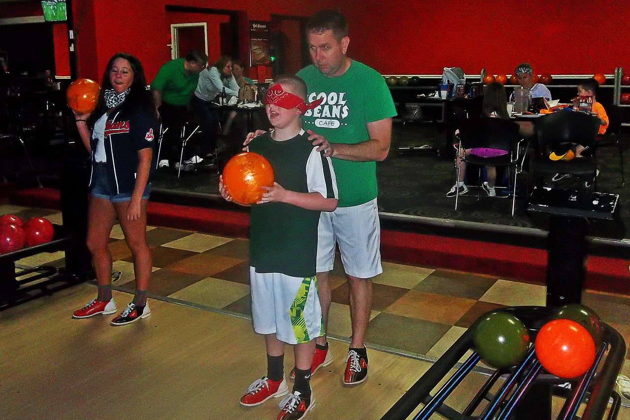 NIKKI RHOADES / GAZETTE Ben Cavey guides his blindfolded son Owen during a fundraiser event held Saturday at AMF Medina Lanes to benefit children with eyesight conditions. The pair were sponsored by Cool Beans Cafe and were first-time attendees at Bowling for Blindness.