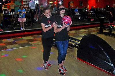NIKKI RHOADES / GAZETTE Trinity Bonitz, who is blind in one eye and has 20/80 vision in the other, serves as a guide to her blindfolded partner Maddy Todorovich during a fundraiser event held Saturday at AMF Medina Lanes.