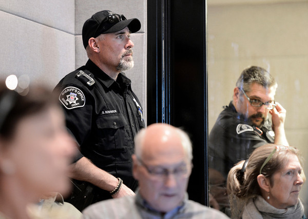 "Boulder County Sheriff's Deputy Robinson, left, and Boulder County Security Guard Chriss Robb, right, watch over the crowd during a Boulder County Commissioners meeting about fracking on Thursday, Jan. 24, at the Boulder County Courthouse on Pearl Street in Boulder. For a video with an anti-fracking supporter go to  <a href=""http://www.dailycamera.com"">http://www.dailycamera.com</a><br /> Jeremy Papasso/ Camera"