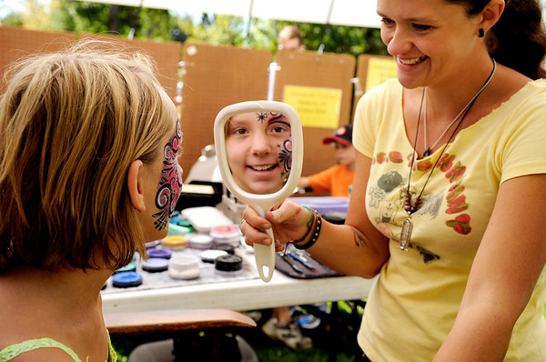 "Maddie Lamphere, 10, of Boulder, smiles in the mirror as Amber Jarvis shows her face painting skills on Saturday, Sept. 3, during the Boulder Creek Hometown Fair in Boulder. For more photos and video of the fair go to  <a href=""http://www.dailycamera.com"">http://www.dailycamera.com</a><br /> Jeremy Papasso/ Camera"