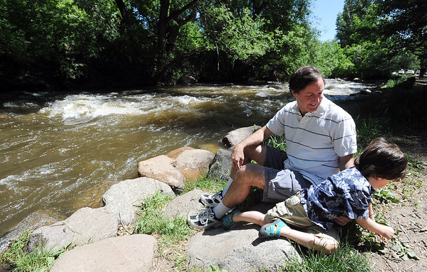 """Alan and Travis Taylor, relax by Boulder Creek in Eben Fine Park.<br /> There were several visitors to Boulder Creek and Eben Fine Park on June 8, 2011, but few actually got in the water.<br /> For a video and more photos of the creek, go to  <a href=""""http://www.dailycamera.com"""">http://www.dailycamera.com</a>.<br /> Cliff Grassmick / June 8, 2011"""