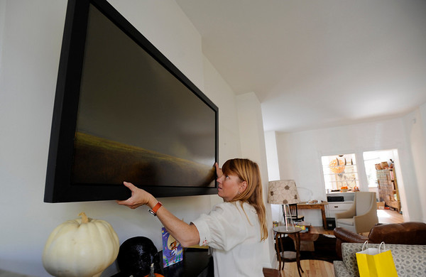 Kris Sustronk takes artwork off her wall to while preparing to evacuate her home near 4th and Mapleton as the Dome Fire cause authorities called for an evacuation of the area under threat from the Dome Fire in Boulder, Colorado October 29, 2010.  CAMERA/Mark Leffingwell