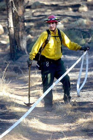 A firefighter works on placing fire hoses as crews continuing working on cleaning up the Dome Fire in Boulder Colorado on Saturday October 30, 2010. <br /> Photo by Paul Aiken / The Camera