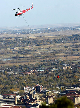 A helicopter makes another water run on the Dome Fire with the skyline of Boulder Colorado in the background on Saturday October 30, 2010. <br /> Photo by Paul Aiken / The Camera