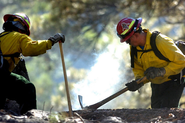 Firefighters concentrate on a smoking hot spot as crews continue working on cleaning up the Dome Fire in Boulder Colorado on Saturday October 30, 2010. <br /> Photo by Paul Aiken / The Camera