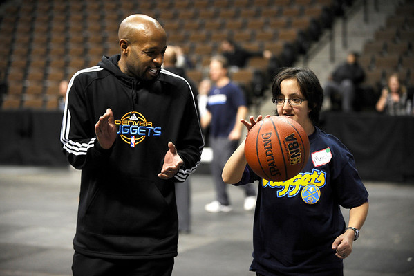 Denver Nuggets Anthony Carter (left) works with Boulder High's Monica Barrios (right) during a Special Olympics Basketball Clinic held at the Pepsi Center in Denver, Colorado February 23, 2010.  CAMERA/Mark Leffingwell