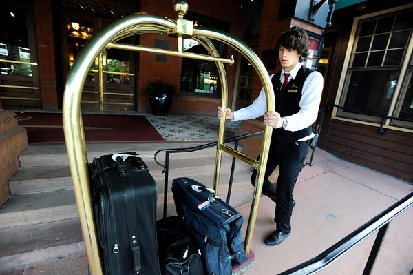 Hotel Boulderado employee Nick Wrammage uses a cart to wheel a customers luggage to their car after checking out of the hotel on Thursday, May 3, in Boulder.<br /> Jeremy Papasso/ Boulder Daily Camera